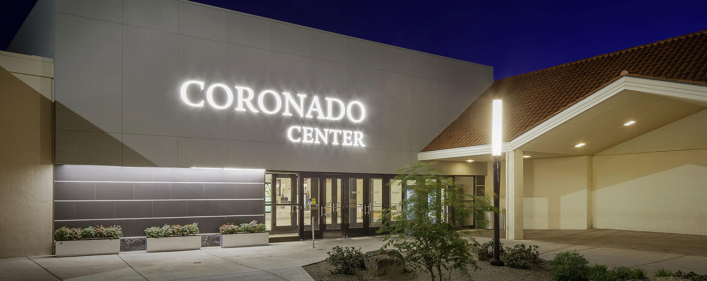 At night, the Coronado Center sign is illuminated at the property entrance decorated with plants and flowers.
